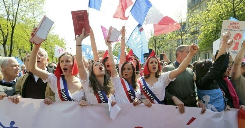 """21.abr.2013 - Manifestantes se vestem como na época da Revolução francesa, no século 18, e seguram cópias do Código Civil do país para protestar contra a legalização do casamento de pessoas do mesmo sexo. O movimento, chamado de """"Manif pour Tous"""" (Demonstração para Todos), organizou um protesto neste domingo (21) nas ruas de Paris. Na faixa, lê-se """"Todos nós nascemos de um homem e uma mulher"""". O Parlamento francês deve votar nesta terça-feira (23) projeto que prevê as legalizações do casamento e da adoção de crianças por pessoas do mesmo sexo"""