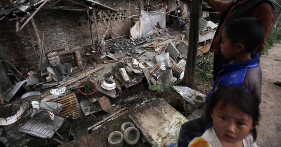 21.abr.2013 - Moradores observam destruição na casa deles, em Yaan, cidade do sudoeste chinês, atingida pelo terremoto de magnitude 6,6 na escala Richter que abalou a região neste sábado (20). Equipes de resgate ainda tentam encontrar sobreviventes, mas enfrentam dificuldades para trabalhar em áreas remotas, que ficaram isoladas por causa de deslizamentos de terra