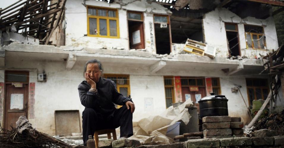 21.abr.2013 - Ri Chenfu, moradora desta casa danificada, conseguiu retirar algumas panelas de dentro do imóvel, que fica em Yaan, cidade do sudoeste chinês, atingida pelo terremoto de magnitude 6,6 na escala Richter que abalou o país neste sábado (20). Equipes de resgate ainda tentam encontrar sobreviventes, mas enfrentam dificuldades para trabalhar em áreas remotas, que ficaram isoladas por causa de deslizamentos de terra