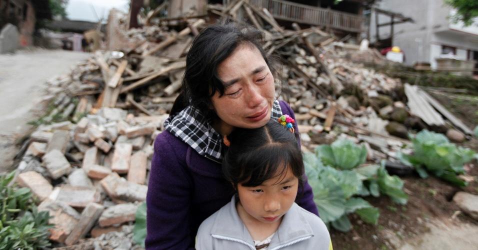 21.abr.2013 - Song Zhengqiong chora abraçada à filha em frente a sua casa, em Longmen, no condado de Lushan, na China. A residência foi parcialmente destruída neste sábado (20), após ser atingida pelo terremoto de magnitude 6,6 na escala Richter que abalou o país neste sábado (20). Autoridades confirmaram ao menos 179 mortos e 6.700 feridos neste domingo (21)