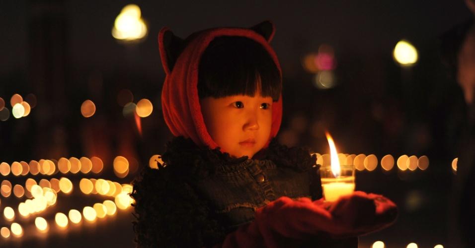 21.abr.2013 - Criança segura vela enquanto pessoas oram pelas vítimas do terremoto que atingiu a província chinesa de Sichuan, no sábado (20), em Daqing, no norte da China, na noite de domingo (21). Um terremoto de magnitude 6.6 atingiu a província chinesa de Sichuan no último sábado (20). O sismo causou mais de 180 mortes e deixou mais de 11 mil pessoas feridas; 21 pessoas estão desaparecidas. Mais de 2,3 mil réplicas (tremores de menor intensidade) registrados em Lushan, na província de Sichuan, dificultam os trabalhos de resgate de vítimas