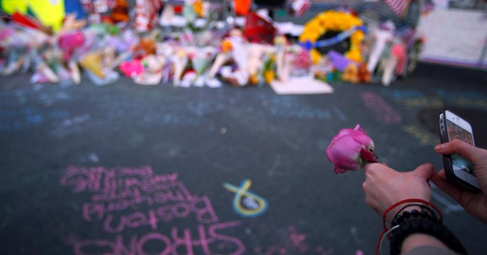 21.abr.2013 - Mulher segura flor em memorial em homenagem às vítimas do atentado na Maratona de Boston, na Boylston Streeton Boylston Street, em Boston, Massachusetts, na noite de domingo (21)