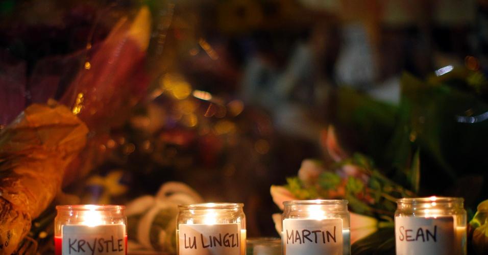 21.abr.2013 - Velas com nomes das vítimas do atentado na Maratona de Boston são colocadas em memorial em homenagem às vítimas na Boylston Street, em Boston, Massachusetts, na noite de domingo (21)