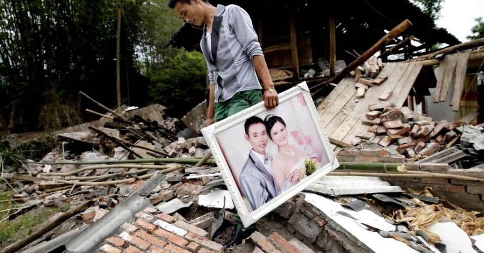 22.abr.2013 - Homem recupera quadro com foto do casamento em meio aos destroços de sua casa após o forte terremoto de magnitude 6.6 que atingiu a província de Sichuan (China) no último sábado (20). O sismo causou pelo menos 186 mortes e deixou mais de 11 mil pessoas feridas; 21 pessoas estão desaparecidas