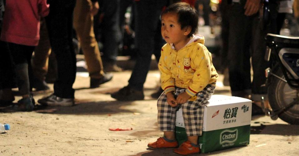 22.abr.2013 - Menina sentada em caixa contendo água mineral espera distribuição de suprimentos básicos nesse domingo (21), após o terremoto de magnitude 6.6 que atingiu a província de Sichuan, na China, no último sábado (20). O sismo causou mais de 180 mortes e deixou mais de 11 mil pessoas feridas. Mais de 2,3 mil réplicas (tremores de menor intensidade) registrados em Lushan, na província de Sichuan, dificultam os trabalhos de resgate de vítimas