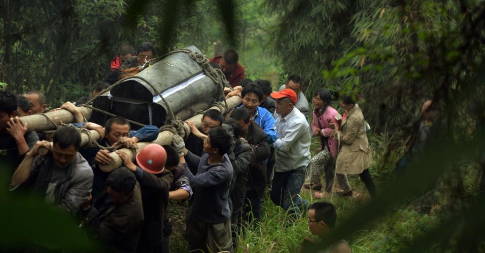22.abr.2013 - Moradores de vilarejo em Lushan, na província chinesa de Sichuan, carregam caixão de homem que morreu no terremoto de magnitude 6.6 que atingiu a província no último sábado (20). O sismo causou pelo menos 186 mortes e deixou mais de 11 mil pessoas feridas; 21 pessoas estão desaparecidas. Mais de 2,3 mil réplicas (tremores de menor intensidade) registrados em Lushan, na província de Sichuan, dificultam os trabalhos de resgate de vítimas