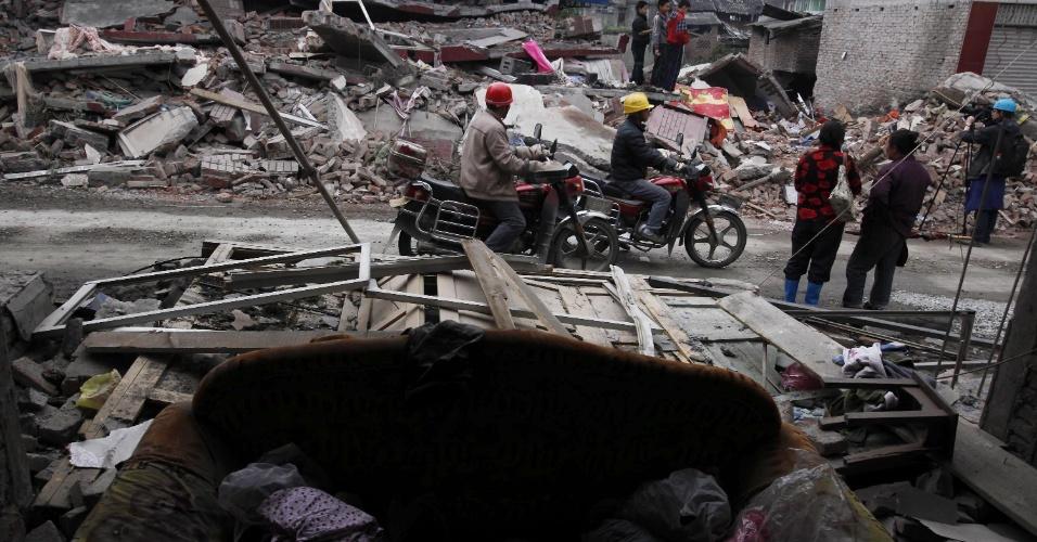 22.abr.2013 - Moradores passam por edifícios derrubados na localidade de Lingguan, na província de Sichuan, na China, após terremoto de magnitude 6.6 que atingiu a província chinesa de Sichuan no último sábado (20). O sismo causou mais de 180 mortes e deixou mais de 11 mil pessoas feridas; 21 pessoas estão desaparecidas. Mais de 2,3 mil réplicas (tremores de menor intensidade) registrados em Lushan, na província de Sichuan, dificultam os trabalhos de resgate de vítimas