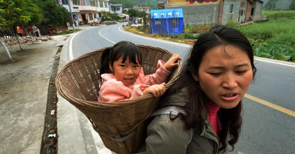 22.abr.2013 - Mulher carrega filha em cesta enquanto caminha até posto de distribuição de comida em vilarejo perto de Longmen, na China, nesta segunda-feira (22). Um terremoto de magnitude 6.6 atingiu a província chinesa de Sichuan no último sábado (20). O sismo causou mais de 180 mortes e deixou mais de 11 mil pessoas feridas. Centenas de sobreviventes fizeram uma passeata exigindo mais assistência das autoridades