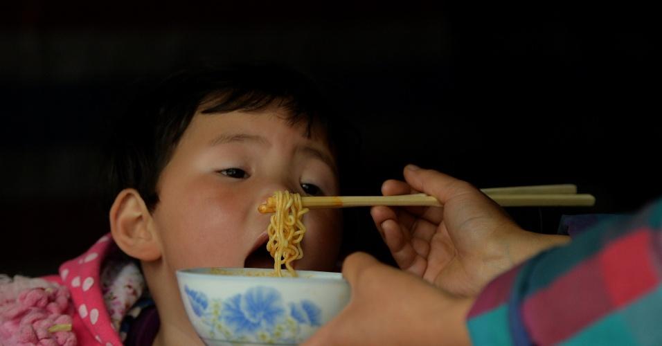 22.abr.2013 - Mulher dá comida para filho em tenda improvisada na cidade de Lushan, na China, nesta segunda-feira (22). Um terremoto de magnitude 6.6 atingiu a província chinesa de Sichuan no último sábado (20). O sismo causou mais de 180 mortes e deixou mais de 11 mil pessoas feridas. Mais de 2,3 mil réplicas (tremores de menor intensidade) registrados em Lushan, na província de Sichuan, dificultam os trabalhos de resgate de vítimas
