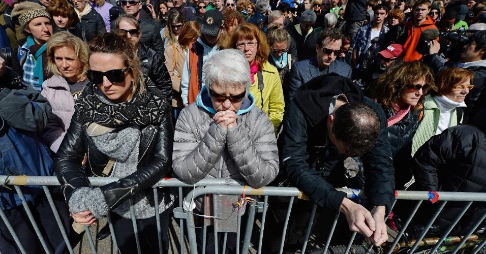 22.abr.2013 - Grupo de pessoas faz um minuto de silêncio, perto da linha de chegada da Maratona de Boston, em homenagem às vítimas das explosões. O ato aconteceu às 14h50 no horário local (15h50 no horário de Brasília), exatamente uma semana após a detonação da primeira bomba na linha de chegada da Maratona da cidade. Centenas de pessoas participaram do tributo