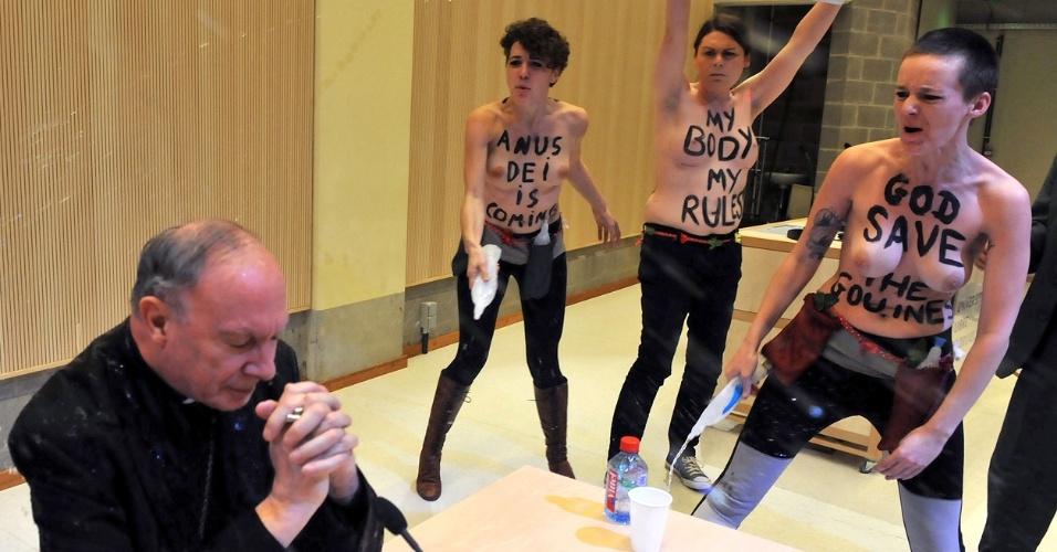 23.abr.2013 - Ativistas do grupo feminista Femen fazem um protesto contra a homofobia durante palestra do arcebispo Andre-Joseph Leonard (à esq.) em uma universidade de Bruxelas (Bélgica)