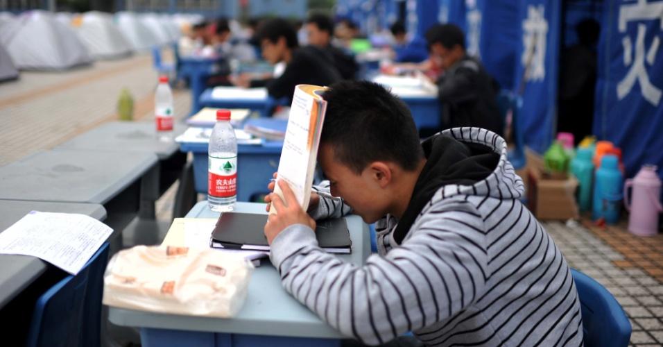 23.abr.2013 - Estudantes se preparam para vestibular ao lado de tendas montadas para abrigar vítimas de terremoto em Tianquan, na província de Sichuan, na China