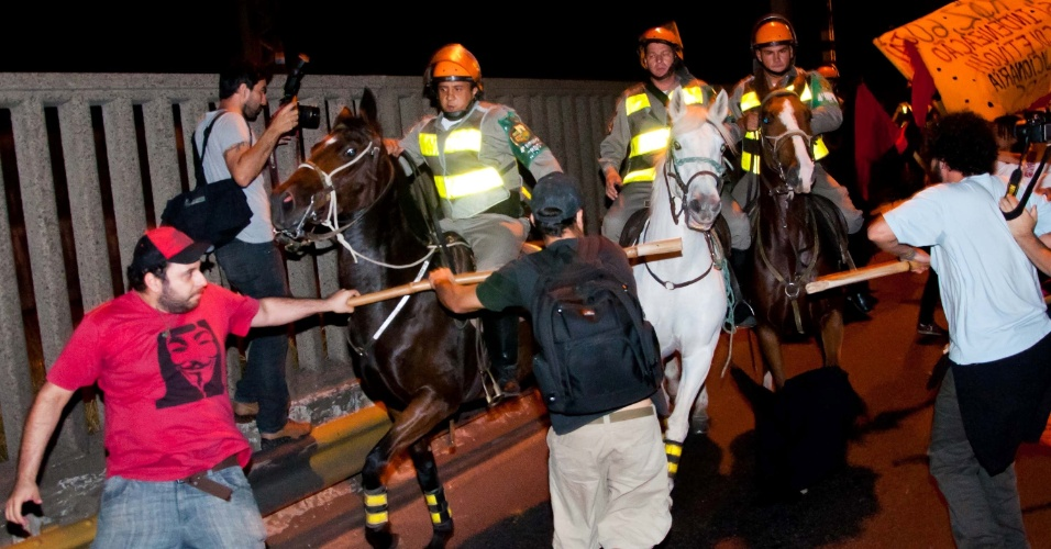 23.abr.2013 - Manifestantes enfrentam a polícia em protesto contra o aumento da passagem de ônibus, realizado em frente à sede da Prefeitura de Porto Alegre