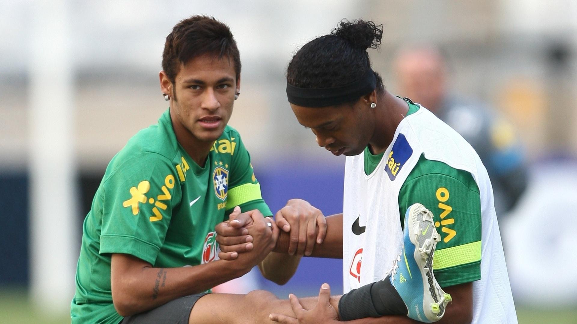23.abr.2013 - Meia Ronaldinho Gaúcho ajuda o atacante Neymar no aquecimento no treino da seleção brasileira no Mineirão