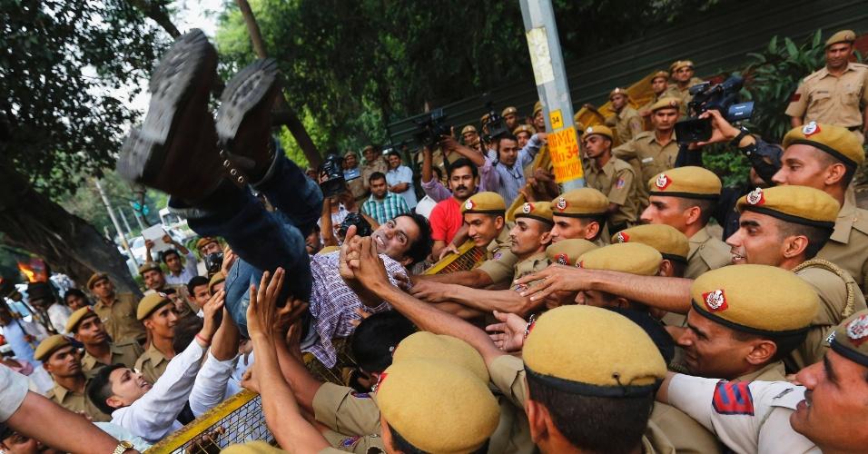 23.abr.2013 - Polícia indiana empurra apoiador do partido de oposição indiano Bharatiya Janata Party (BJP) que tentava atravessar uma barricada durante protesto fora da residência da ministra-chefe de Nova Déli, pedindo mais segurança na cidade. Uma menina de cinco anos foi estuprada e torturada em Nova Déli, na semana passada