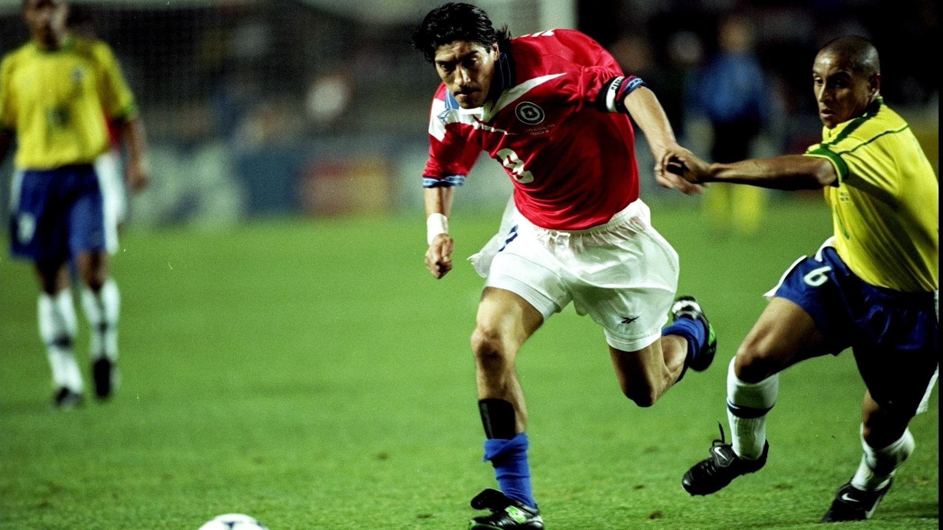 27.jun.1998 - Atacante Zamorano, do Chile, passa pela marcação do lateral Roberto Carlos durante a derrota por 4 a 1 para o Brasil, pelas oitavas da Copa do Mundo 1998