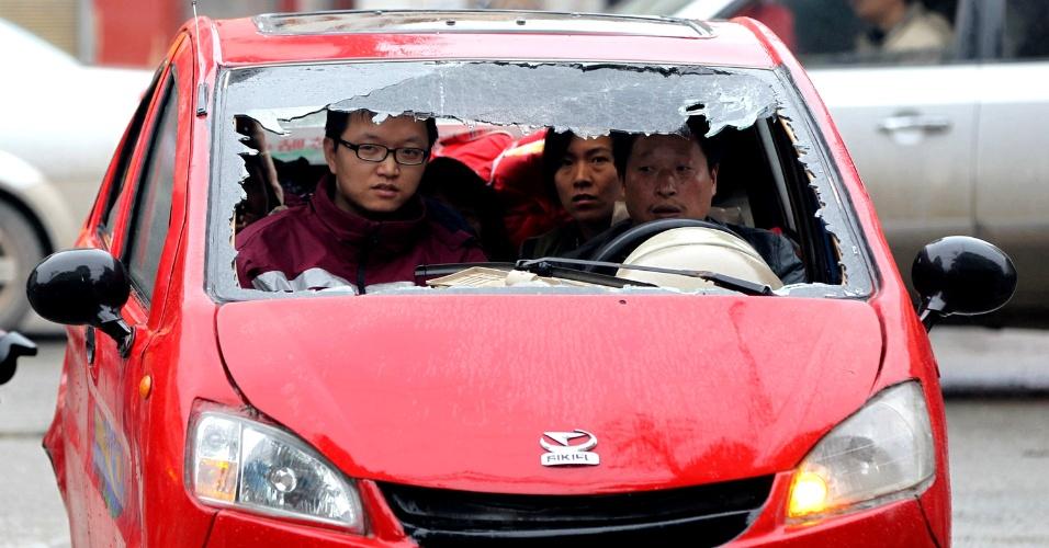 23.abr.2013 - Chineses trafegam em carro com o para-brisa quebrado na cidade de Lingguan, província de Sichuan, no sul da China, após o terremoto do último sábado (20). Milhares de pessoas seguem desabrigadas e sem perspectiva de onde viverão