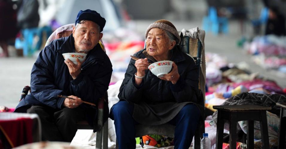 23.abr.2013 - Idosos comem refeição em abrigo temporário na cidade de Ligguan, ao sul da província de Sichuan, no sul da China. Milhares de sobreviventes desabrigados do terremoto do último sábado (20) estão sobrevivendo em barracas nas ruas e sofrendo com racionamento de comida