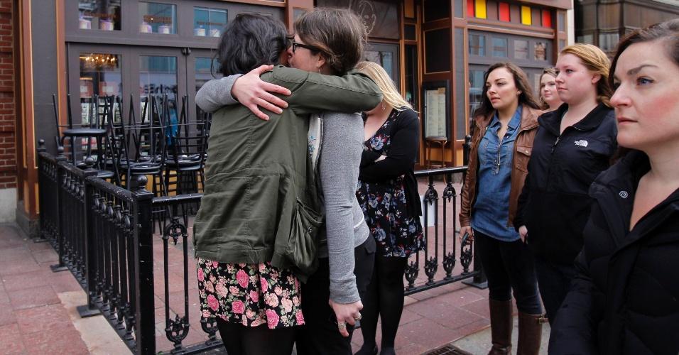 24.abr.2013 - Funcionárias do Starbucks e de outras lojas que funcionam na Boylston Street em frente ao local onde ocorreu a primeira explosão de bomba na Maratona de Boston (EUA), se abraçam na reabertura do comércio pela primeira vez desde os atentados