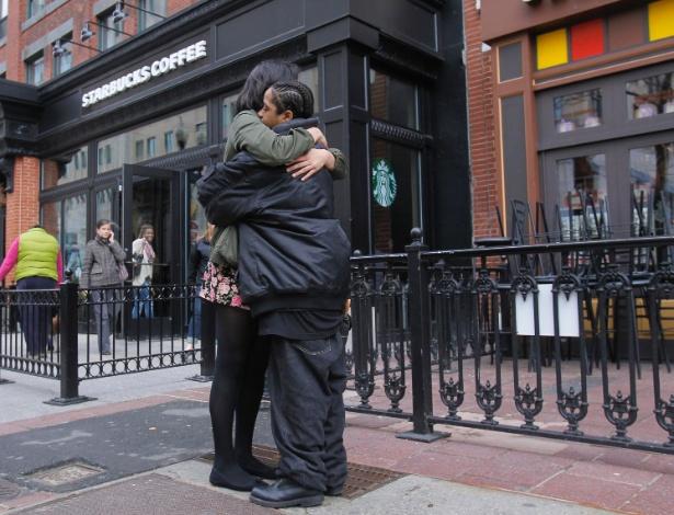 24.abr.2013 - Funcionárias do Starbucks que funciona na Boylston Street em frente ao local onde ocorreu a primeira explosão de bomba na Maratona de Boston (EUA), se abraçam na reabertura da loja pela primeira vez desde os atentados