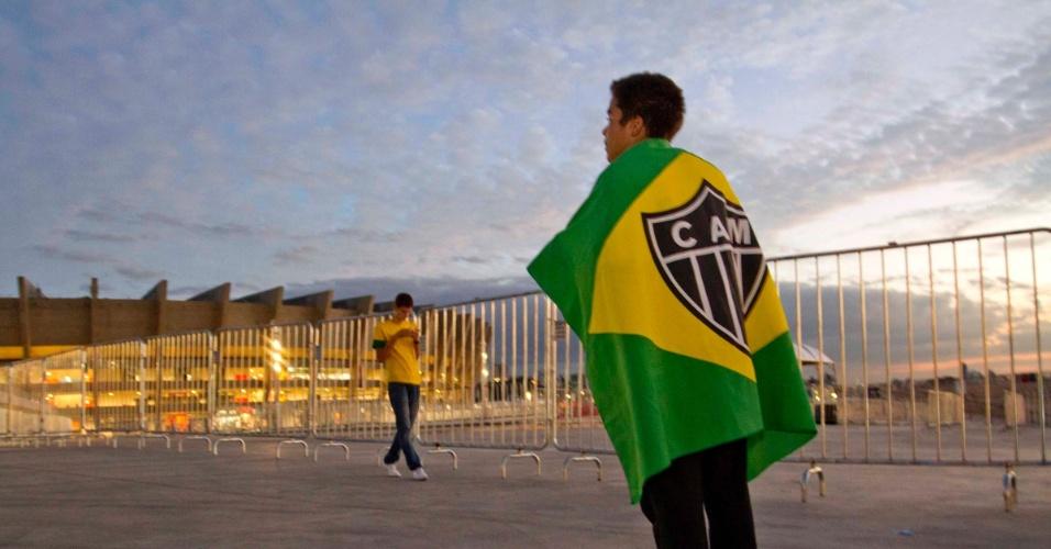 24.abr.2013 - Torcedor com a bandeira do Galo observa movimentação em frente ao estádio do Mineirão, que receberá o amistoso entre Brasil e Chile nesta quarta-feira