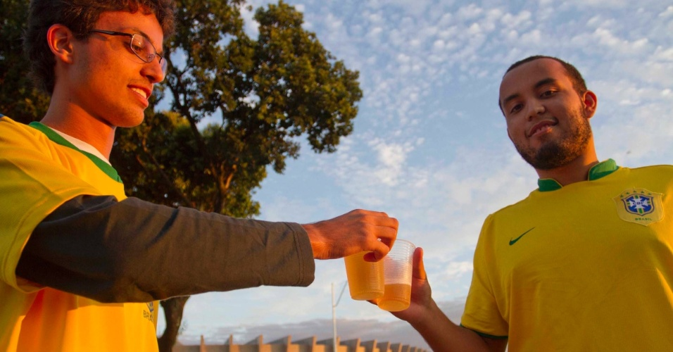 24.abr.2013 - Torcedores brindam com copos de cerveja na entrada do Mineirão, horas antes do início do amistoso entre Brasil e Chile