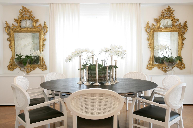 A arquiteta Brunete Fraccaroli uniu o clássico e o contemporâneo nesta sala de jantar com espelhos em desenho clássico e móveis em linhas atuais, em um jogo preto e branco e o dourado
