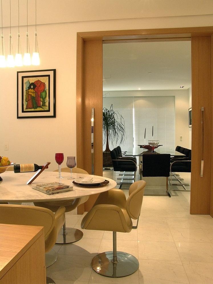 A porta de correr de madeira e o piso em mármore ligam a sala de almoço ao jantar na proposta da ARZ Design para a família que recebe muitos amigos em casa. Do lado do almoço, a composição da mesa Saarinen em mármore de Carrara e cadeiras Tulipa