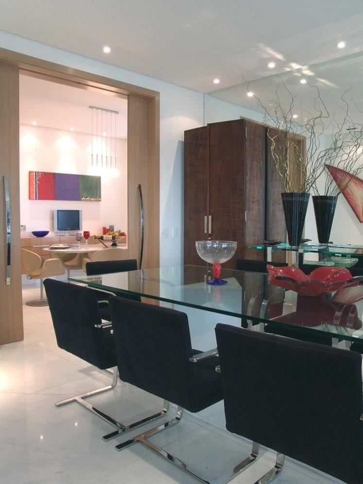 Como a família gosta de receber amigos, a proposta da ARZ Design foi integrar a sala de jantar com a sala de almoço por meio de um grande vão que pode ser fechado por porta de correr. A mesa de vidro com pé de mármore é completada pelas cadeiras Brno. Ao fundo, a parede espelhada amplia o espaço
