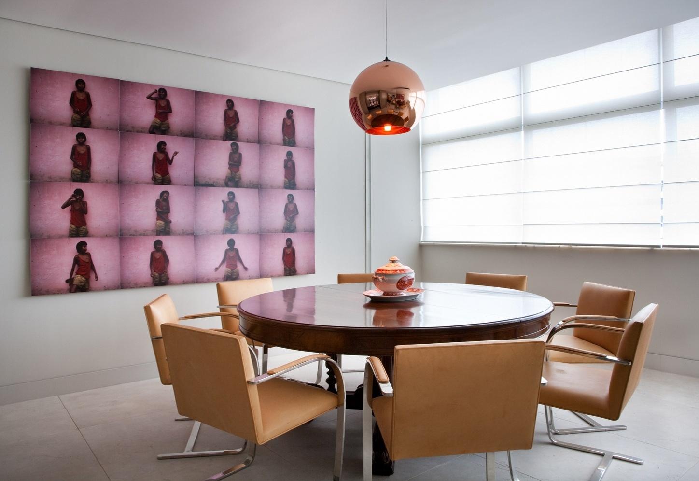 Nesta sala de jantar, o arquiteto Toninho Noronha trabalhou com o contraste entre a mesa redonda em estilo inglês e as cadeiras Brno, de Mies Van der Rohe, revestidas de couro, tudo reaproveitado do antigo apartamento da cliente. Sobre ela, a luminária pendente do designer Tom Dixon é da Lumini. Na parede, a série de fotos cor de rosa é assinada por Miguel Rio Branco