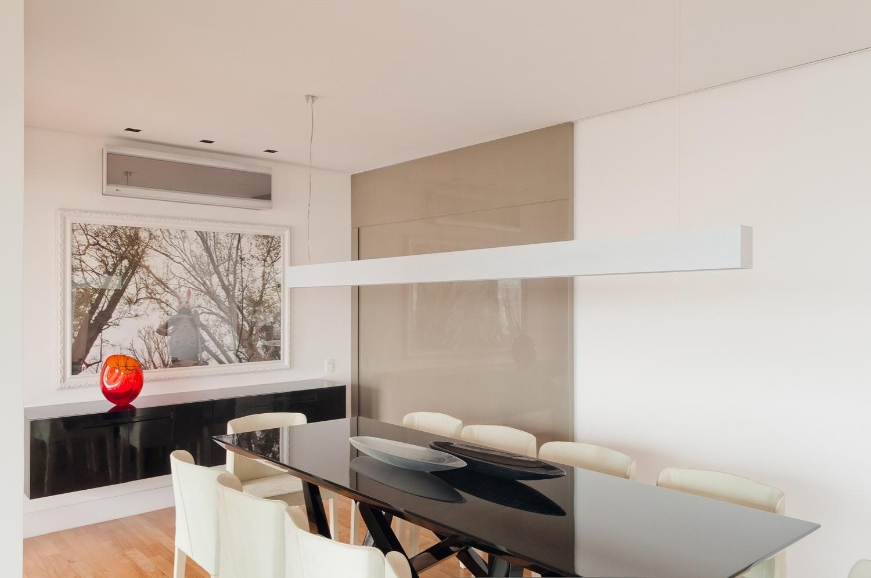 No ambiente assinado pelo arquiteto Toninho Noronha, a mesa de jantar Torah, do designer Pedro Mendes (Micasa), compõe com o aparador desenhado pelo arquiteto e fabricado em madeira com acabamento em laca P.U. preta brilhante (Marcenaria Kuzendorff).  As cadeiras são da Dpot e a foto na parede é do artista Felipe Morozini, da Zipper Galeria