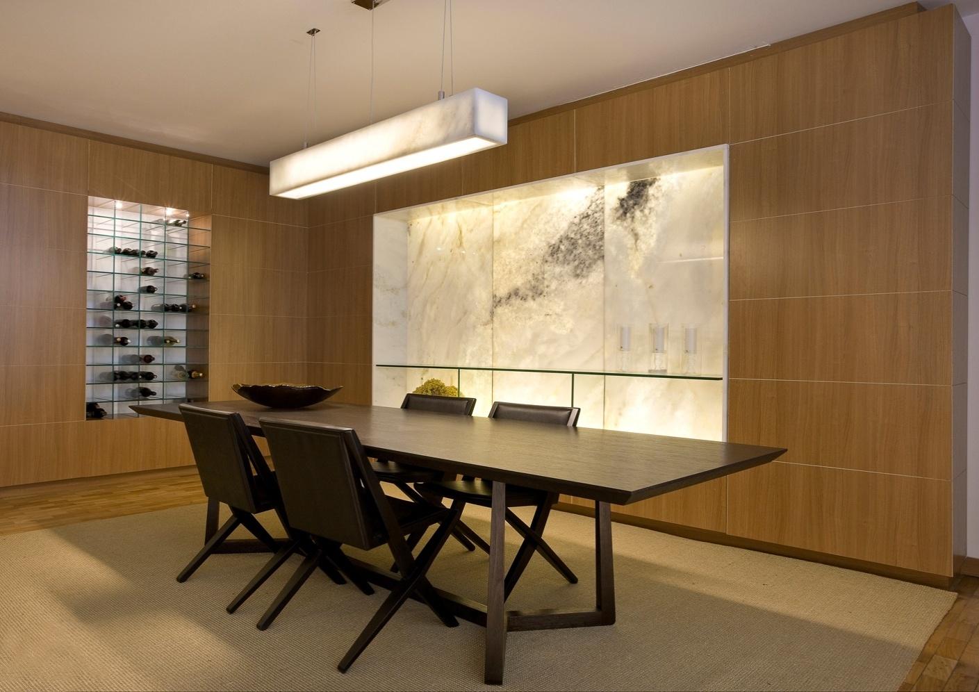 No projeto, assinado pela arquiteta Cristina Menezes, o que chama atenção é o nicho de mármore iluminado onde está acoplado o aparador de vidro e o louceiro embutido, que compõe com os móveis e o padrão amadeirado dos módulos de MDP, levando requinte ao ambiente. O outro nicho também tem prateleiras de vidro que abrigam garrafas