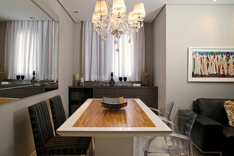 O ambiente de jantar, planejado pela arquiteta Cinthia Garcia e a designer Andréia Karalkovas, diferencia-se pela mescla de materiais e tipologias de mobiliário: duas cadeiras são de acrílico e duas cadeiras revestidas de tecido listrado, da Espaço e Forma. A mesa, desenhada pelo escritório e executada pela Blanco Design, é de madeira com acabamento em laca brilho e meio do tampo de madeira teca