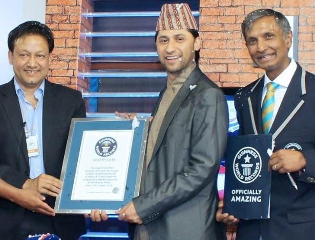 """O apresentador da TV nepalesa Rabi Lamichhane (centro), recebe do Livro dos Recordes um  certificado por bater o recorde mundial de horas seguidas comandando um programa de televisão, em Katmandu, no Nepal. Ele ficou no ar por mais de 62 horas entrevistando políticos, jornalistas e celebridades sobre o tema """"Buda nasceu no Nepal"""""""