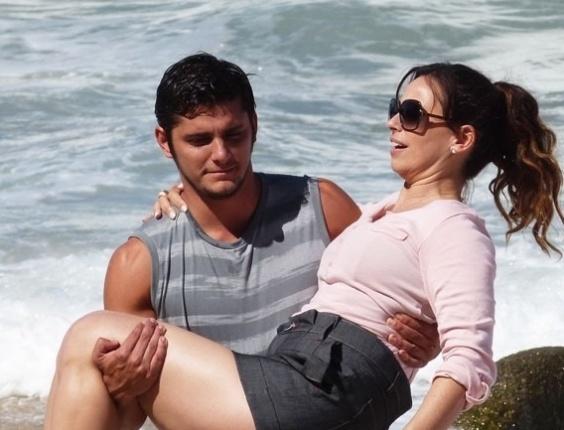 """24.abr.2013 - Bruno Gissoni carrega Daniela Escobar no colo durante gravação de """"Flor do Caribe"""" em uma praia deserta do Rio de Janeiro. Na trama, o casal Juliano e Natália sairá de Vila dos Ventos para ter um dia romântico longe de olhares curiosos"""