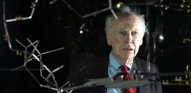 O cientista James Watson posa ao lado do modelo original de DNA