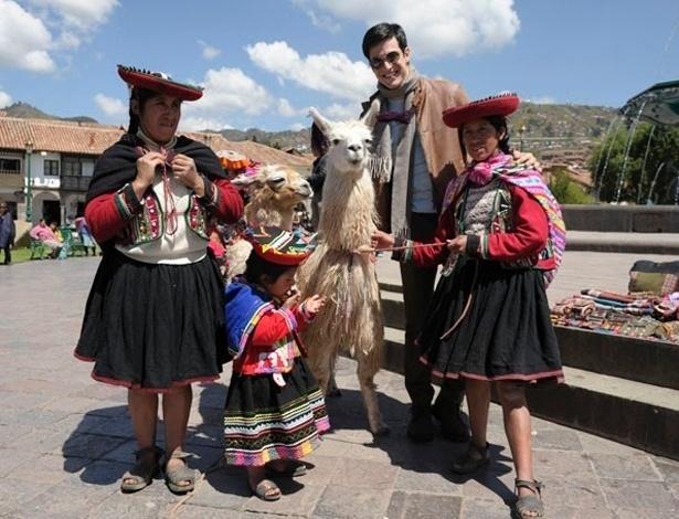 """25.abr.2013 - Mateus Solano posa com lhamas e mulheres em trajes típicos durante as gravações de """"Amor à Vida"""" no Peru"""