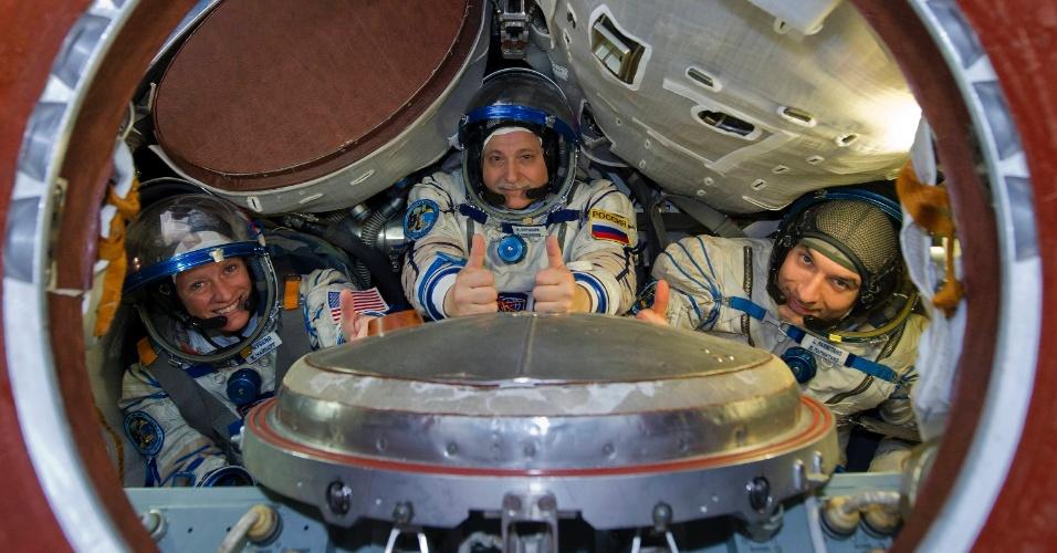 26.abr.2013 - O próximo trio de astronautas que será enviado à Estação Espacial Internacional (ISS, na sigla em inglês) entram em uma cabine para exercícios de simulação no centro de treinamento em Star City, na região de Moscou, capital da Rússia, nesta sexta-feira (26). A norte-americana Karen Nyberg, o russo Fyodor Yurchikhin e o italiano Luca Parmitano (da esquerda para a direita) devem embarcar na nave Soyuz rumo à ISS no dia 28 de maio