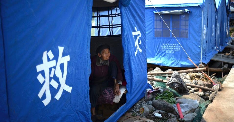 26.abr.2013 - Idosa observa o movimento em tenta de abrigo, fornecida a moradores da província de Sichuan após o terremoto do último sábado (20), que causou a morte de 196 pessoas. Ao menos 11 mil ficaram feridos e 21 pessoas estão desaparecidas