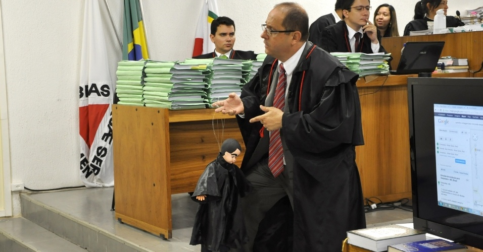 27.abr.2013 - Ércio Quaresma, advogado do ex-policial Marcos Aparecido dos Santos, o Bola, acusado de assassinar Eliza Samudio, usa boneco para se referir ao promotor Henry Castro, durante exposição aos jurados, no último dia do julgamento, em Contagem (MG). O advogado e o promotor trocaram farpas e, em sua tréplica, Quaresma chamou o promotor de