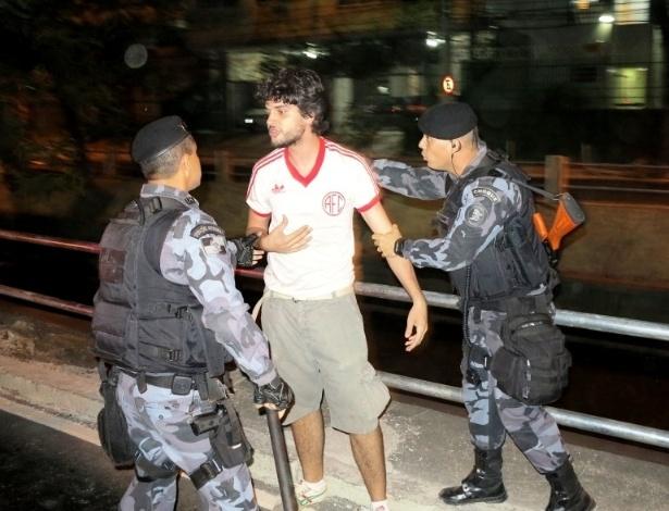 27.abr.2013 - Manifestante é contido por policiais durante protestos nos arredores do Maracanã