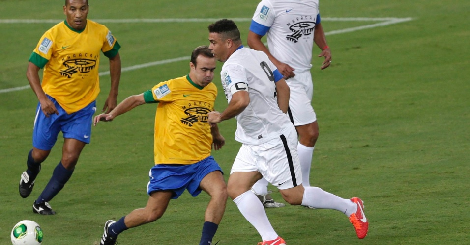 27.abr.2013 - Ronaldo dribla Roger Flores durante o jogo contra os amigos de Bebeto, que serviu como evento teste na reabertura do Maracanã