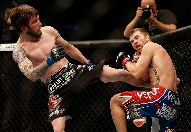 28.abr.2013 - Johny Bedford (e.) chuta lateral do corpo de Bryan Caraway durante luta do UFC 159
