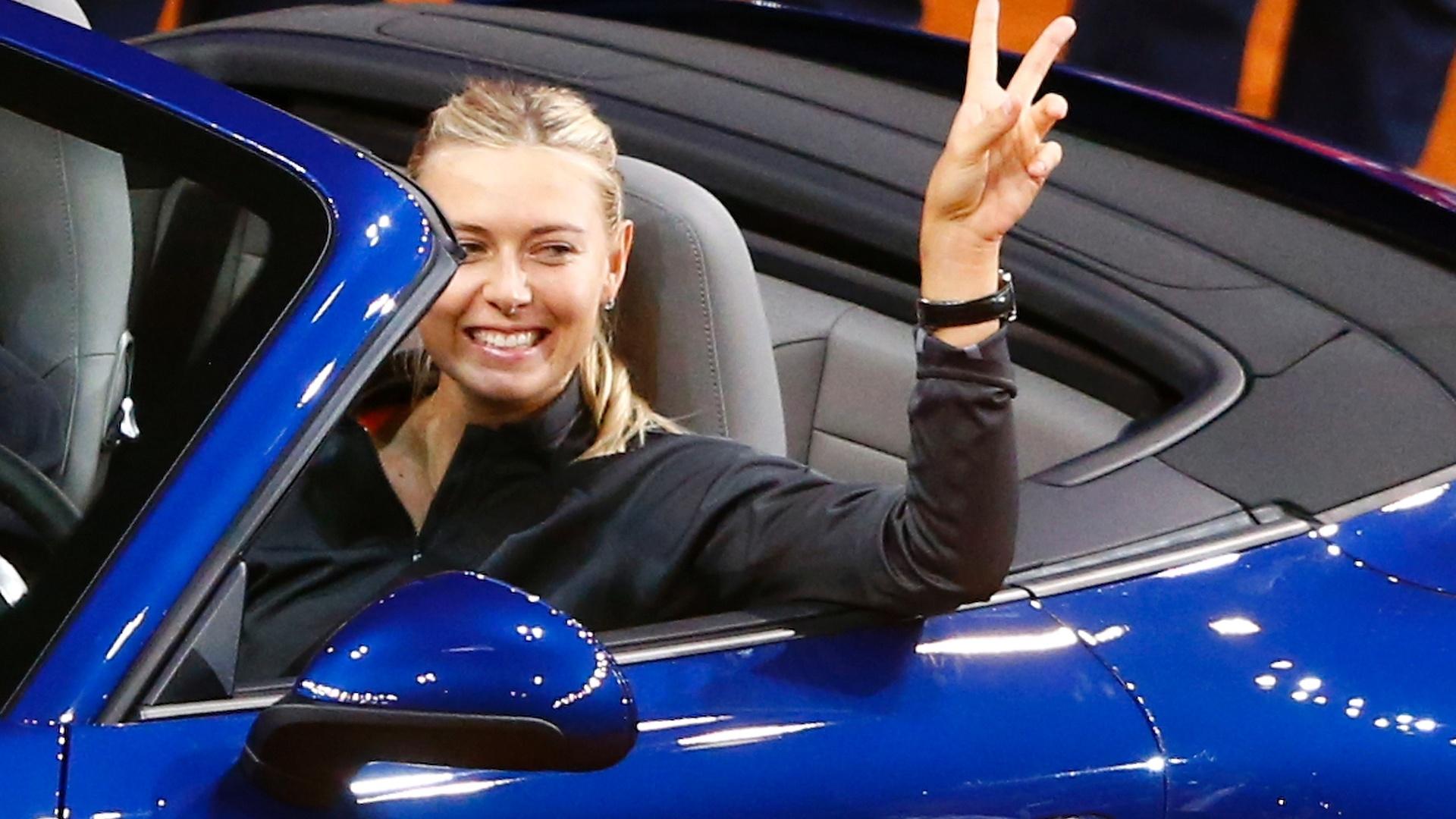 28.abr.2013 - Russa Maria Sharapova acena do Porsche 911 4S que ganhou após vencer a final do Torneio de Stuttgart, na Alemanha