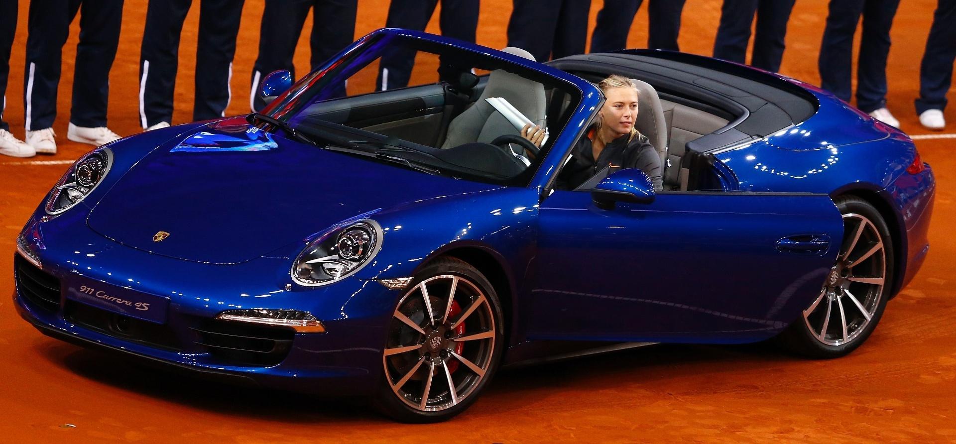 28.abr.2013 - Sharapova testa Porsche 911 4S que ganhou após vencer a final do Torneio de Stuttgart, na Alemanha