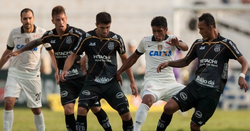 Jogadores da Ponte tentam bloquear avanço do volante Paulinho. Jogo define um dos semifinalistas do Paulistão