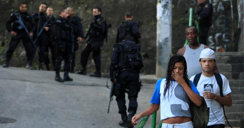 29.abr.2013 - Pessoas passam por policiais durante ocupação da comunidade do Cerro Corá, no Cosme Velho, zona sul do Rio de Janeiro. Segundo a PM, as três favelas eram dominadas pela facção criminosa Comando Vermelho e serviam de refúgio para os criminosos