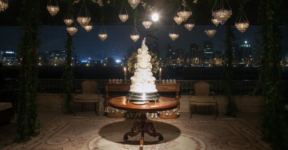 Imagem de decoração de casamento com lustres e bolo em destaque