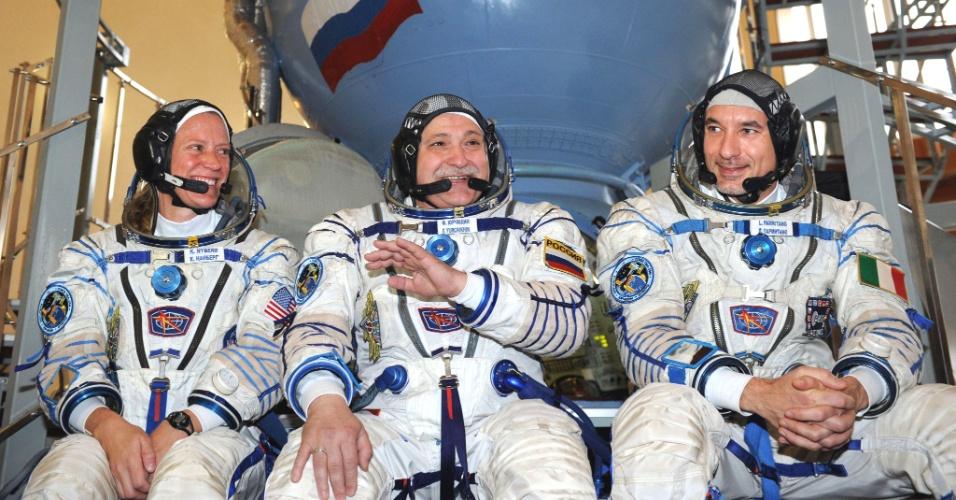 30.abr.2013 - A astronauta norte-americano Karen Nyberg (à esquerda), o cosmonauta russo Fyodor Yurchikhin (centro), e o italiano Luca Parmitano (R) sorriem diante de simulador da nave Soyuz, durante treinamento no Star City, no subúrbio de Moscou. Os três devem decolar da base russa de Baikonur, localizada no Cazaquistão, no dia 29 de maio, em direção da Estação Internacional (ISS)