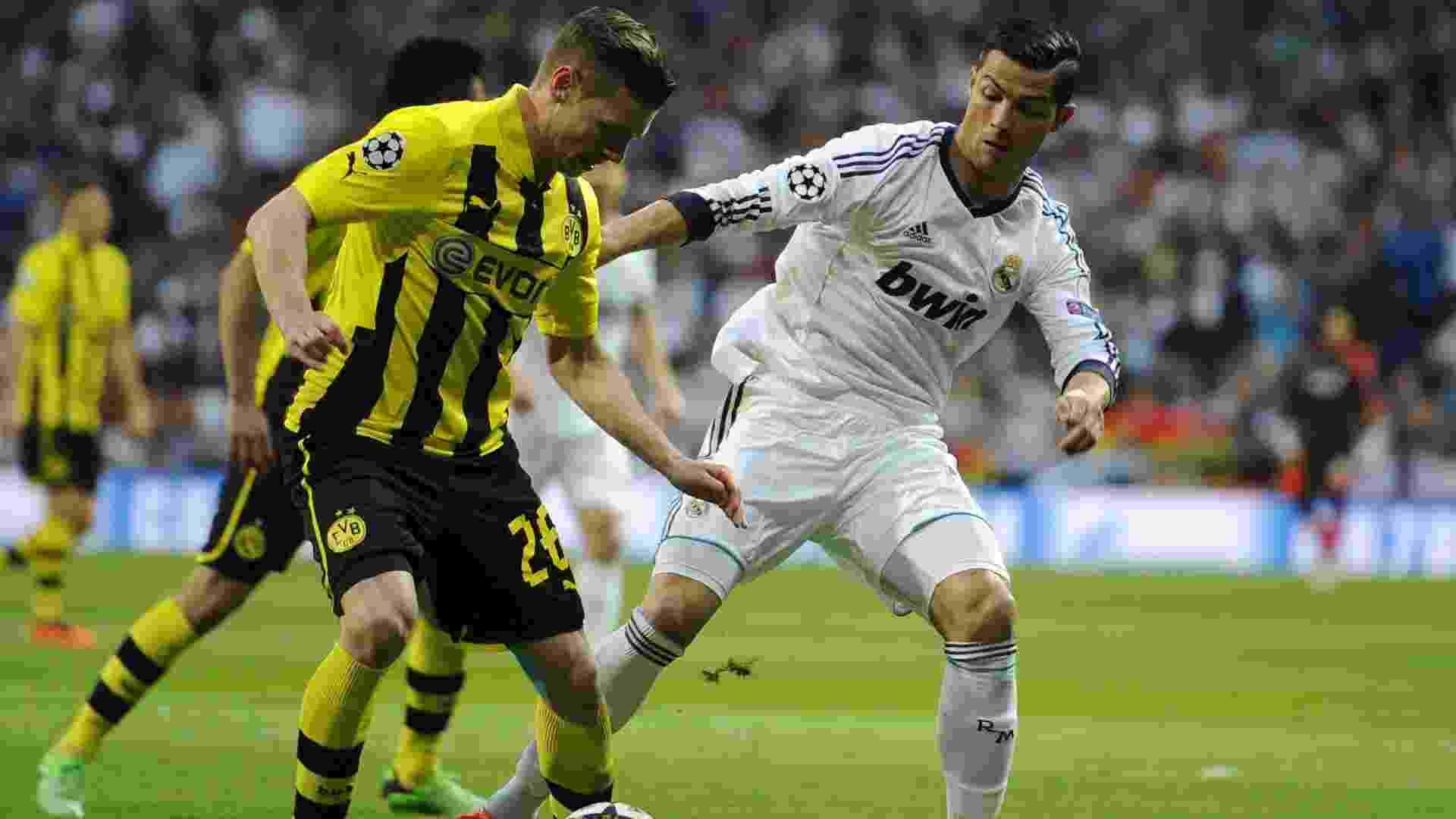 30.abr.2013 - Cristiano Ronaldo disputa pela bola com Lukasz Piszczek no segundo jogo das quartas entre Real e Borussia - AFP PHOTO / DANI POZO